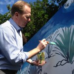 San Diego City Councilmember Kevin Faulconer helps paint the Rose Creek Mural.