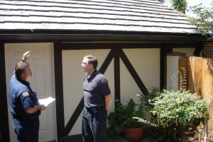University City resident Bob Bayer and Deputy Fire Marshal Eddie Villavicencio discuss fire prevention at Bayer's canyon-rim home. Bayer replaced his wood shake roof with fire-safe tiles to help protect his home from fire. Photo: San Diego Earthworks